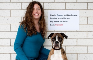 "Julia and Xena, with sign that reads ""I train Boxers in Obedience. I enjoy a challenge. My name is Julia. I am Cornell."""